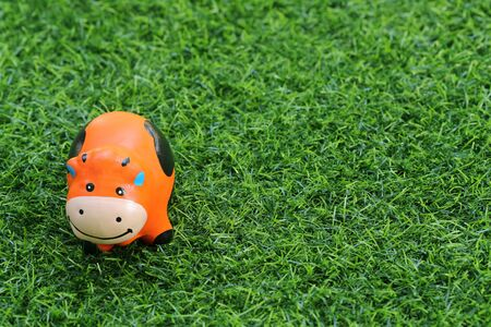 cute toy cow on grass, using as background