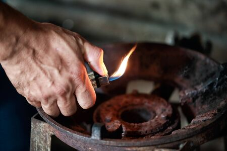 close up hand holding lighter over old gas