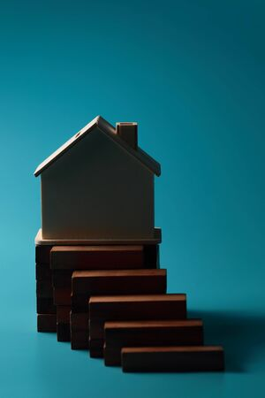 wooden block stacking and house using as background with copy space