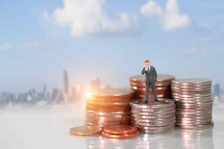 Miniature people: businessman standing on coin stacking podium with city blur background (this image for financial and business competition concept) 스톡 콘텐츠 - 132000542