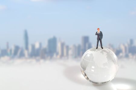 Miniature people: businessman standing on earth with city blur background (this image for financial and business competition concept)