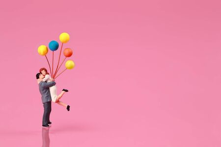 Miniature people: a couple standing and holding balloon on pink background idea for love concept