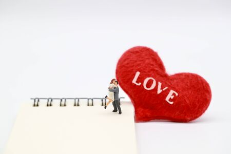 Miniature people: a couple standing on notebook with read heart symbol, idea for valentine background