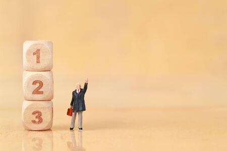 Miniature people: businessman standing with wooden podium using as background (Financial and Business competition concept) Stok Fotoğraf - 132392611