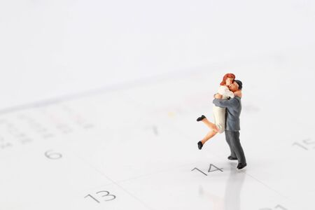 Miniature people: a couple standing on calendar at 14 February , meaning of love