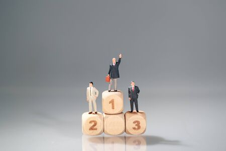 Miniature people: businessman standing on wooden podium (Financial and Business competition concept) Stok Fotoğraf - 132392620