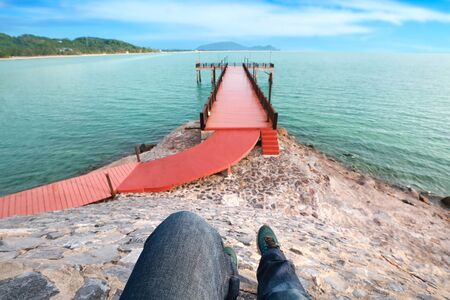 top view portrait of man legs enjoy holiday vacation and wearing jean and sneakers with red bridge and blue sky Stok Fotoğraf