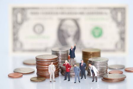 Miniature people: businessman standing on stacking coins , Financial and Business competition concept using as background