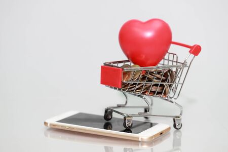 trolley with coins and heart on smart phone, idea for shopping and online payment using as business background Stok Fotoğraf