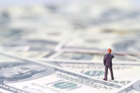 Miniature people: businessman standing and thinking on banknotes (Financial and Business competition concept) Stok Fotoğraf