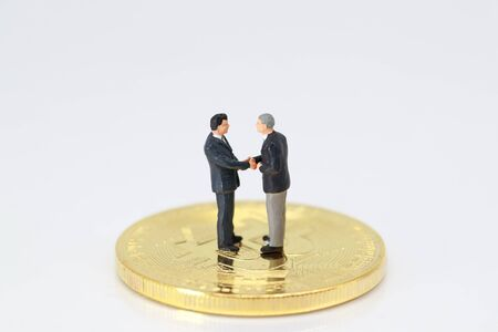 Miniature people: a group of businessman standing on bitcoin (this image for financial and business competition concept) Stok Fotoğraf - 132392647