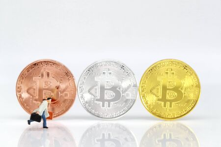 Miniature people: businessman walking with bitcoins blur background (Financial and Business competition concept)