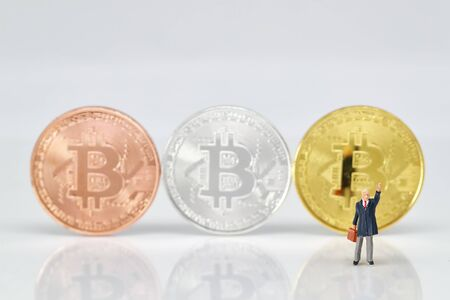 Miniature people: businessman standing with bitcoins blur background (Financial and Business competition concept) Stok Fotoğraf