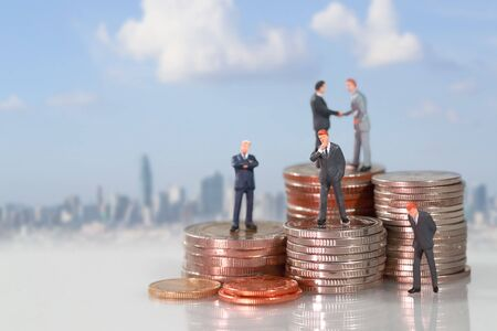 Miniature people: businessman standing on coin stacking podium with city blur background (this image for financial and business competition concept)