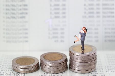 Miniature people: a couple standing on book bank , idea for saving money for love