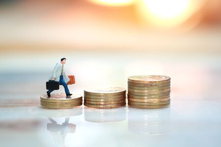 Miniature people: businessman walking or running to the top of stacking golden coins with sun light and reflection (Financial and Business growth concept)