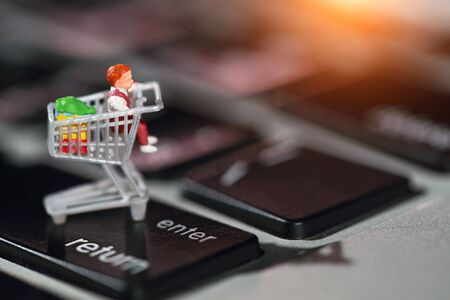 Miniature people: shopper press enter on computer keyboard as payment online from home (e-commerce and shopping concept)