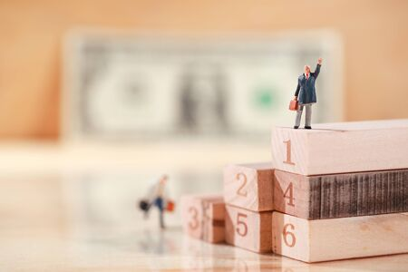 Miniature people: businessman walking or running to the top of wood block stacking (Financial and Business competition concept)