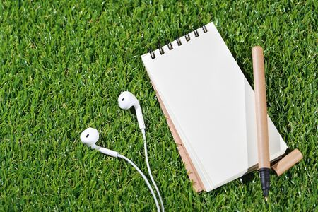 notebook and pen on top with earphone on grass (travel concept) Stok Fotoğraf