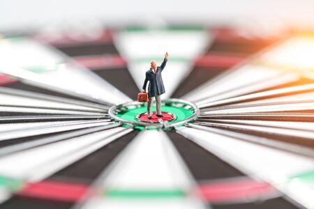 Miniature people: businessman standing on dartboard target center idea of financial and business goal Stok Fotoğraf