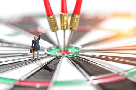 Miniature people: businessman standing on dartboard target center with arrows idea of financial and business goal