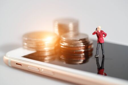 Miniature people: shopper use smart phone and standing on cell phone with money beside idea for payment and purchase online (e-commerce and shopping concept) Stok Fotoğraf - 132392754