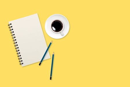 modern workspace table top view with notebook pen and coffee cup on yellow background Stok Fotoğraf