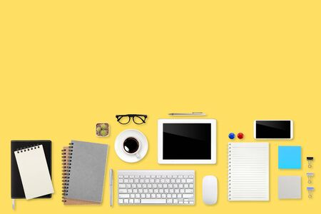 flat lay workspace table with laptop computer, office supplies, coffee cup, tablet and cell phone on yellow pastel background