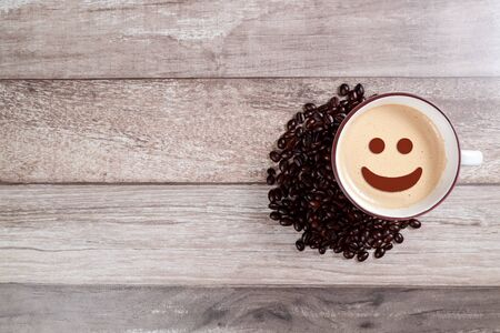 coffee cup with smiling face and bean on wooden table Stok Fotoğraf