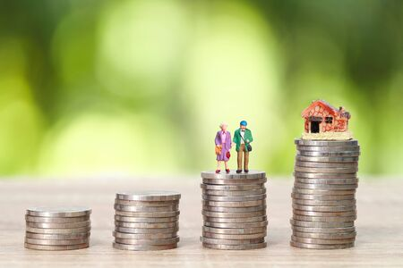miniature old couple standing on stack coins with house and green background (idea for saving money after retire)