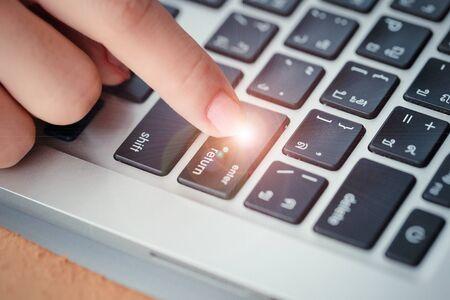 human hand press enter or confirm button on computer keyboard Stok Fotoğraf - 132392778