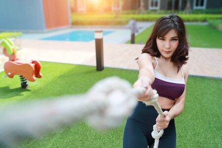 young healthy and sporty woman doing exercise with a rope outdoor (this image for workout and training concept) Stock Photo