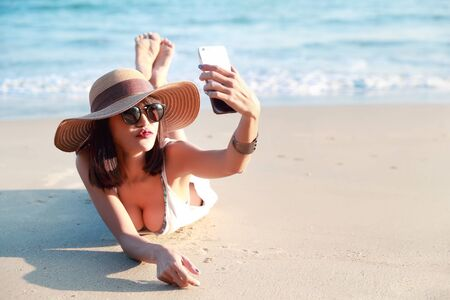 beautiful and sexy woman use cell phone while on holiday vacation do self portrait and kissing to camera on the beach