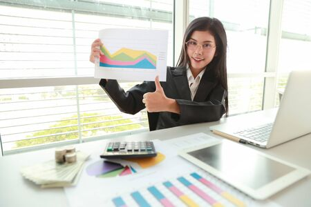 businesswoman showing thumb up and company profit with graph in meeting room 스톡 콘텐츠