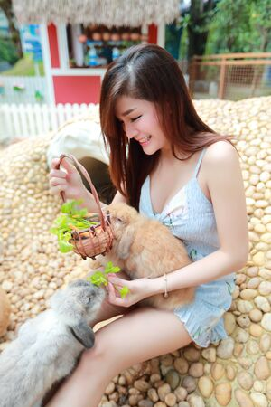 portrait of beautiful woman with smiling face playing with rabbits Reklamní fotografie