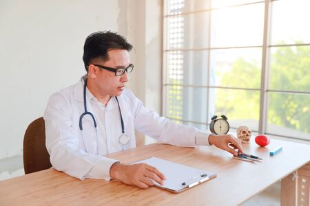 asian doctor portrait working and checking patient list (medical concept)