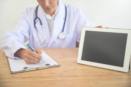 doctor writing note with tablet and inform patient (medical concept)
