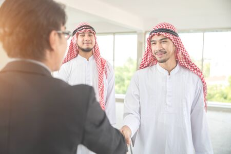 arab saudi businessman shaking hand with businesspeople for successful deal using as business background (concept of teamwork and partnership) Stock fotó