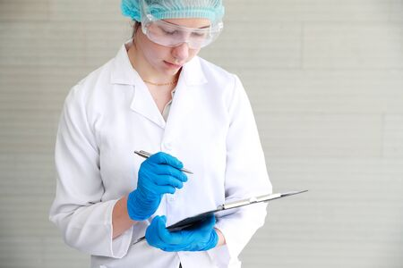 scientist woman checking and recording the results using as science research background. Stock Photo