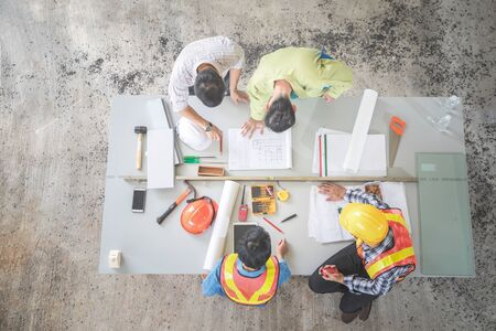 engineer people working and discussing with architecture or blueprint at construction site Banco de Imagens