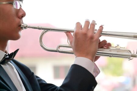 close up young musician man wearing black suit playing trumpet 写真素材
