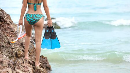Back view of sexy and beautiful girl butt who wearing green bikini and holding blue scuba diver and orange snorkel on tropical beach in summer time with right copy space