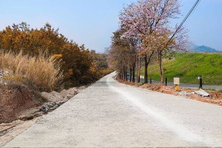 under construction slope road with beautiful mountain view and pink flowers on trees