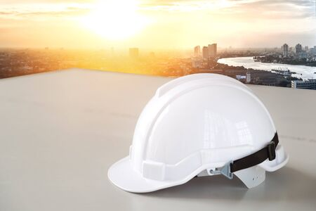 white safety helmet hat for worker and engineer with city and river background