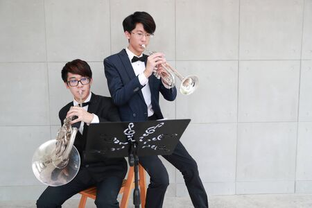 young musician men wearing black suit playing french horns and trumpet