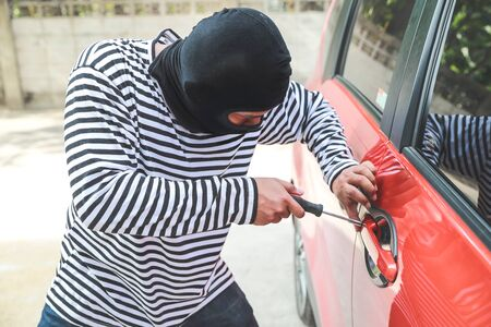 thief try to break into car with screwdriver (theft concept) Stok Fotoğraf
