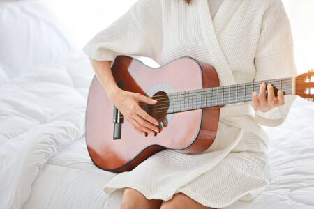 young beautiful girl playing guitar in bedroom (relaxation concept) Stockfoto
