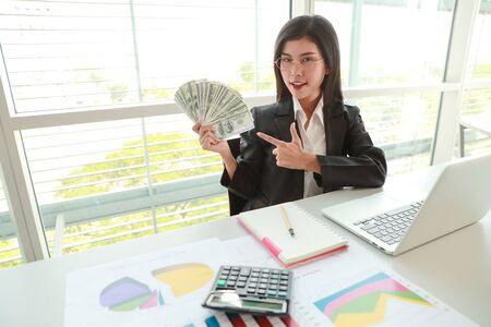 Geschäftsfrau, die einen zusammenfassenden Bericht des Unternehmens und ein Diagramm mit Geld auf Händen zeigt