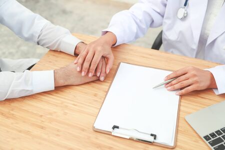 doctor comforting and holding hand male patient with care (medical concept)