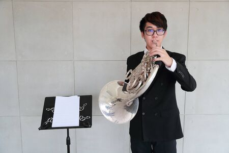 young musician man wearing black suit playing french horns